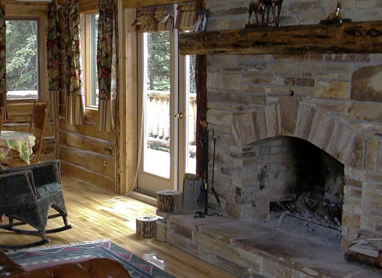 Shown is a large, rustic stone fireplace that needs to be cleaned in a WNY cabin outside of Buffalo, NY