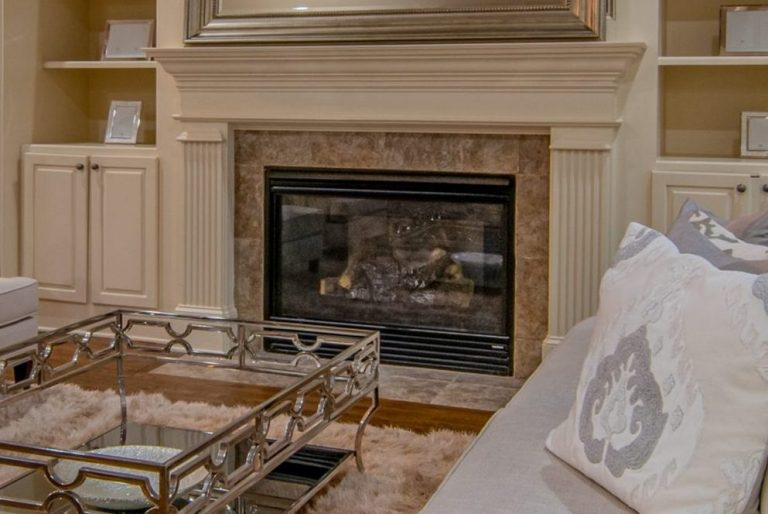 Shown is a white pillared fireplace in a comfortable home in Buffalo New York