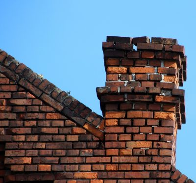 Shown is a brick chimney in Buffalo that is in need of chimney waterproofing and sealant